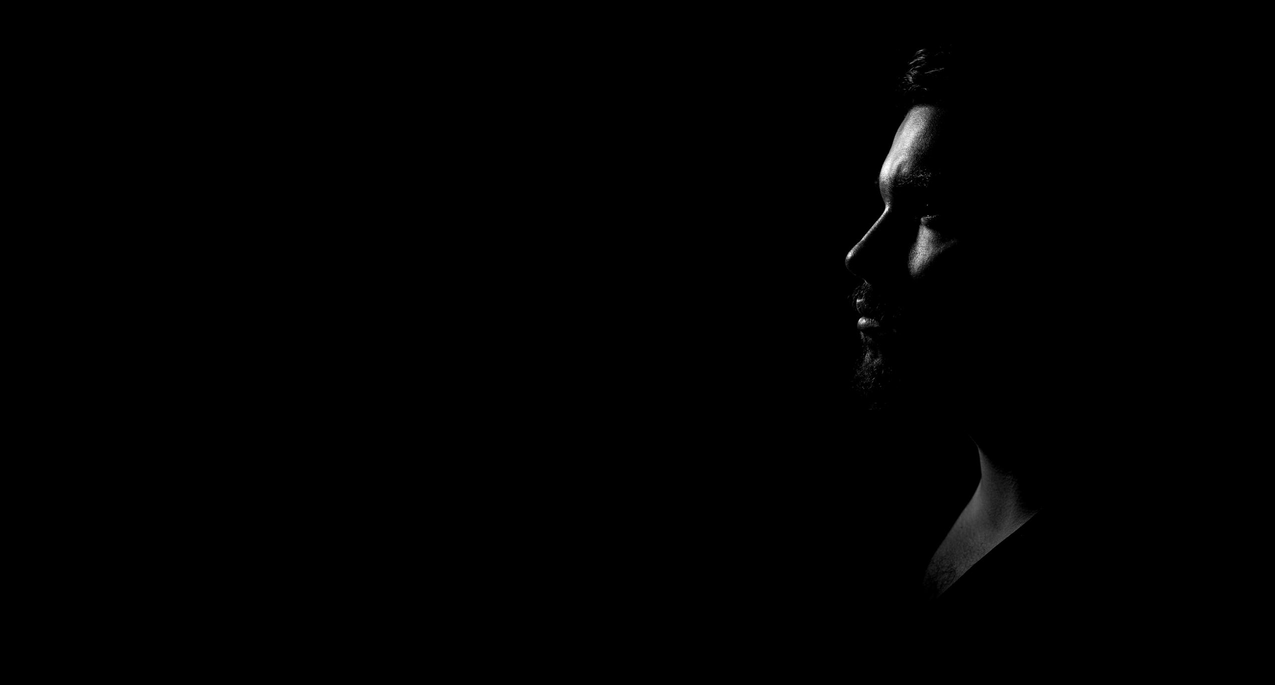 Perfil de homem em preto e banco no fundo preto, virado para a esquerda da tela, com o logo do Dialogo no Escuro a sua frente.